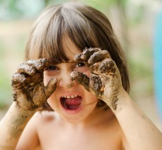 Happy girl playing with mud with dirty hands