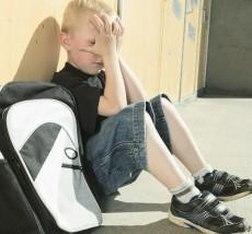 Грустный мальчик с портфелем