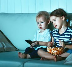 Children brother and sister watching TV in the evening